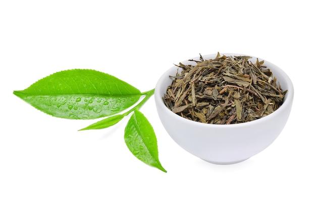 Feuilles de thé vert avec des feuilles de thé séchées isolées sur fond blanc.