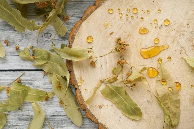 Feuilles de tilleul et fleurs sur tranche de bois