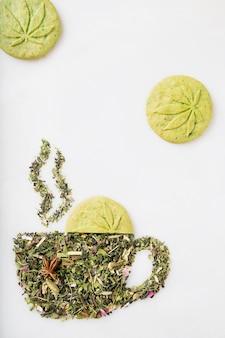Feuilles de tisane sèche en forme de tasse avec de la fumée et des biscuits au cannabis