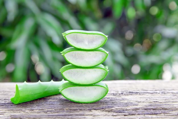 Feuilles et tranches d'aloe vera fraîches sur une table en bois pour les produits de santé.