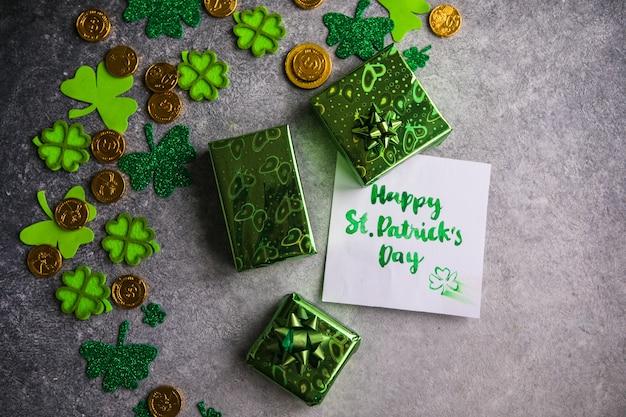 Feuilles de trèfle décoratives, boîte de cadeaux verte, pièces de monnaie sur fond de pierre, pose à plat. célébration de la saint-patrick. carte joyeuse saint-patrick