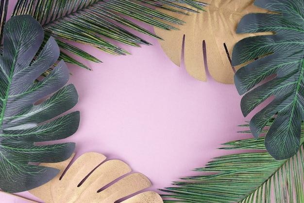 Feuilles tropicales dorées, vertes sur fond rose. palmier tropical. abstrait moderne. fond d'écran de la plage.