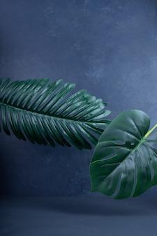 Feuilles vertes artificielles sur bleu.