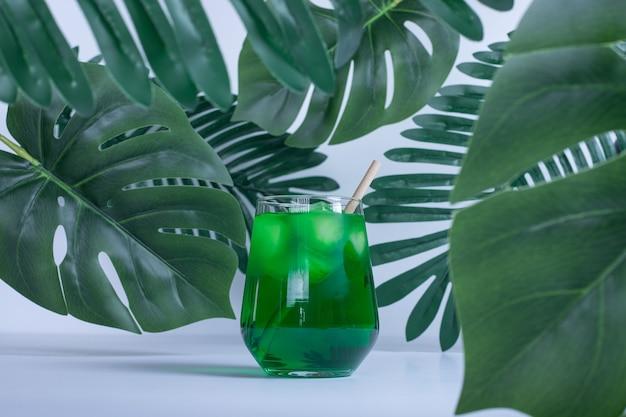Feuilles vertes artificielles et verre de jus sur table blanche.