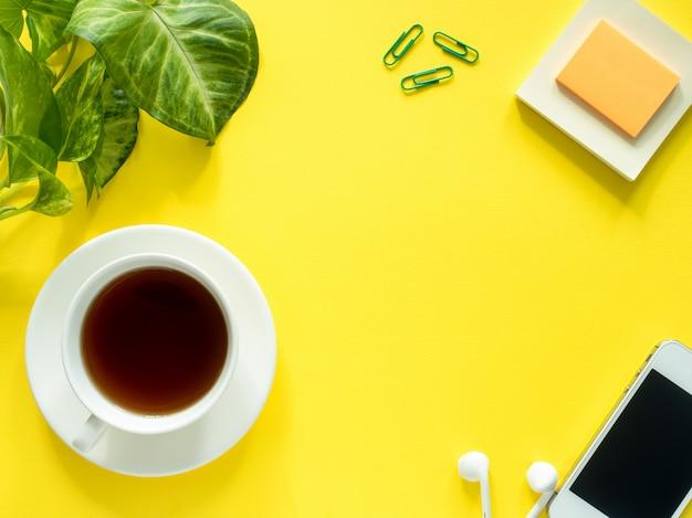 Feuilles vertes plante tasse à café sur le bureau jaune, plat poser, espace copie.