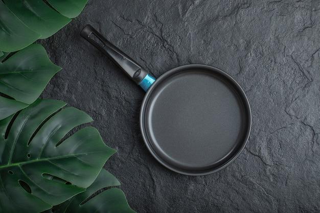 Feuilles vertes et poêle à frire sur fond de pierre noire.