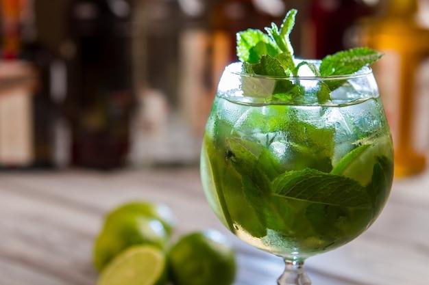 Feuilles vertes en verre à cocktail. boisson avec de la glace. profitez d'une boisson fraîche. hugo à la menthe et citron vert.