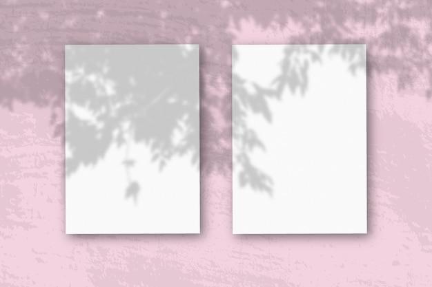 Feuilles verticales de papier blanc texturé sur fond de table rose pâle maquette avec une superposition d'ombres végétales