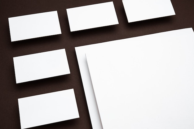 Feuilles vierges flottant au-dessus du fond marron, créatives. cartes blanches. maquette moderne de style bureau pour la publicité. fond blanc vierge pour le concept de design, d'affaires et de finance.