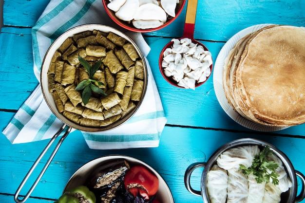 Feuilles de vigne dolma, crêpes, dolma chou dans des casseroles sur une table bleue.