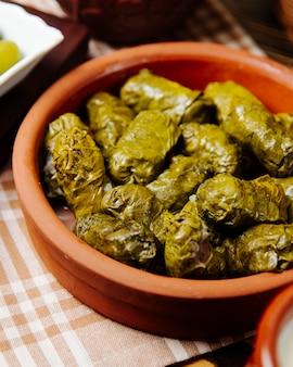 Feuilles de vigne dolma en plaque d'argile viande hachée feuilles de vigne épices vue latérale