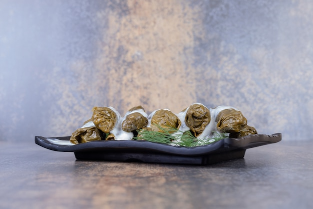 Feuilles de vigne farcies dolma sur assiette avec du yaourt.