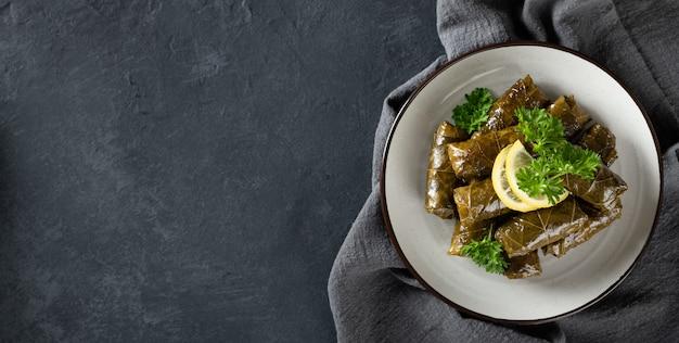 Feuilles de vigne farcies avec du riz et de la viande sur un fond sombre, vue d'en haut, copiez l'espace. cuisine traditionnelle grecque, caucasienne et turque