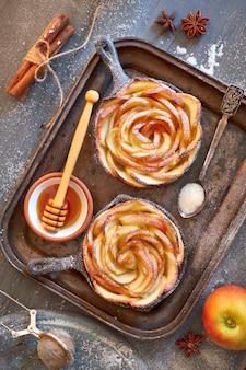 Feuilleté fait maison avec des tranches de pomme en forme de rose cuites dans une poêle en fer