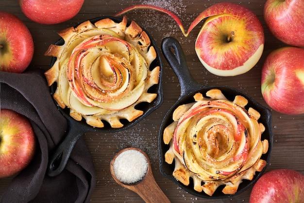 Feuilletés faits maison avec des tranches de pomme en forme de rose cuites dans une poêle en fer