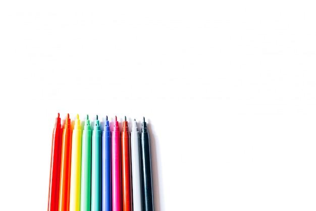 Feutres de différentes couleurs sur une surface blanche