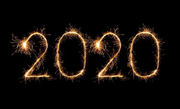 Feux d'artifice de bonne année 2020 écrits avec des feux de bengale la nuit