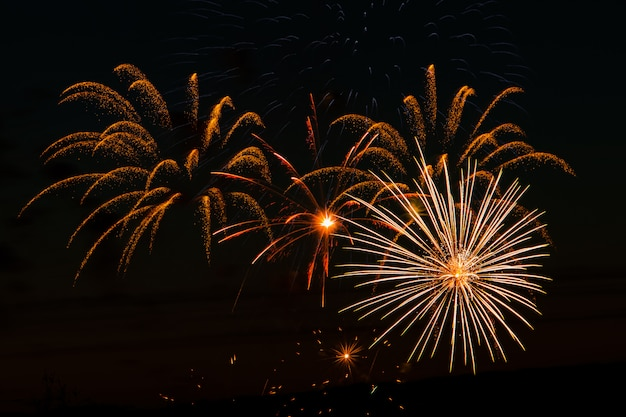 Feux d'artifice festifs dans le ciel nocturne. salut multicolore lumineux sur un espace noir. place pour le texte.