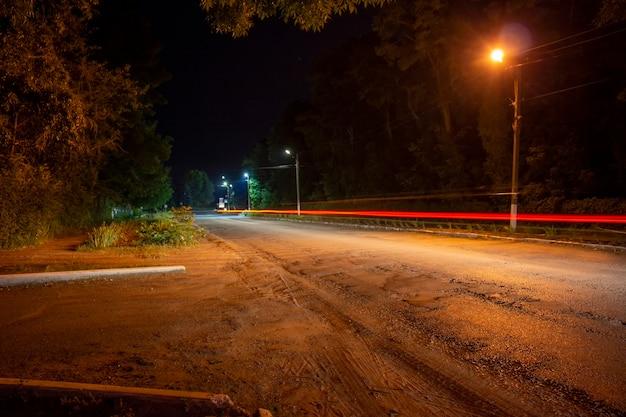 Feux rouges des voitures qui passent sur la route