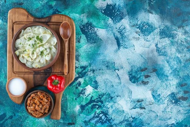 Fèves au lard, dushbara, cuillère, poivre et sel à bord sur bleu.