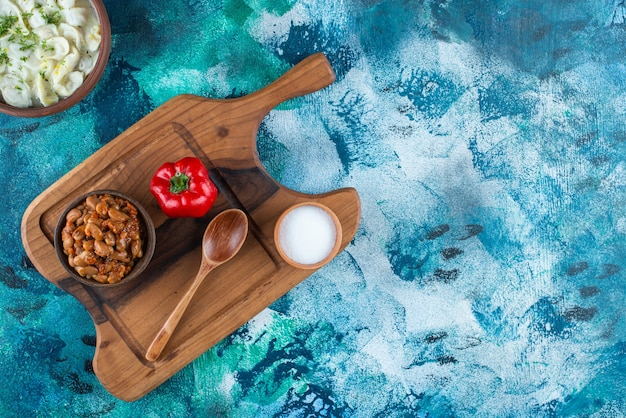 Fèves au lard, dushbara, cuillère, poivre et sel sur une planche, sur la table bleue.