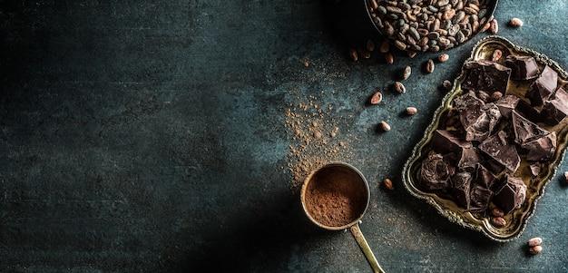Fèves de cacao au chocolat noir et poudre sur table en béton.