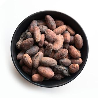 Fèves de cacao dans des bols sur blanc. fermer. vue d'en-haut.
