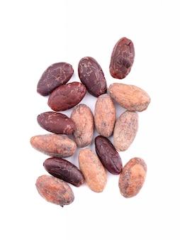 Fèves de cacao non pelées et pelées, isolées. fèves de cacao torréfiées et aromatiques, chocolat naturel. vue de dessus.