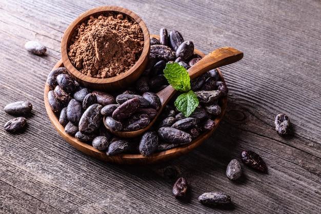 Fèves de cacao et poudre dans une cuillère en bois sur une vieille table rustique
