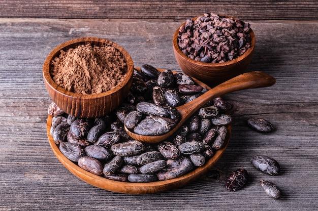 Fèves de cacao sèches entières, poudre, grumeaux dans des bols en bois sur une vieille table rustique.