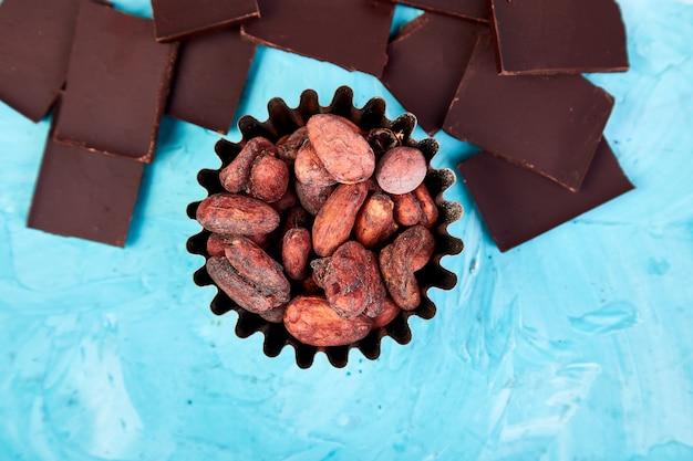 Fèves de cacao sur la table bleue. morceaux de chocolat noir