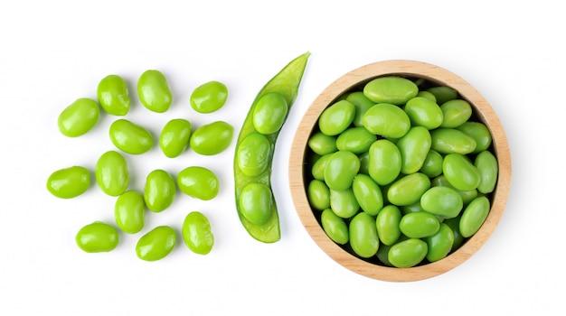 Fèves de soja vert edamame dans un bol en bois sur mur blanc