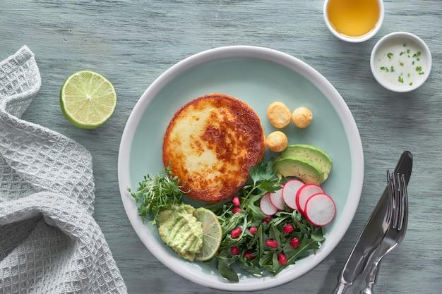 Ffranche de fromage frite avec salade de roquette verte aux graines d'avocat, de radis et de grenade