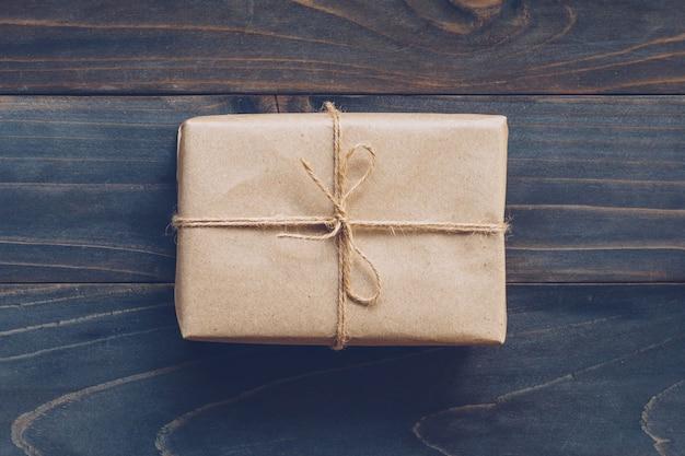 Ficelle ou ficelle attachée dans un arc sur une boîte cadeau en papier kraft sans texture ni fond de table en bois.