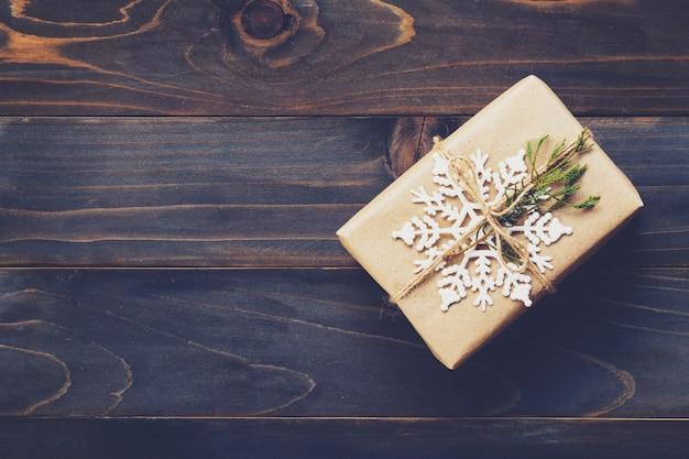 Ficelle ou ficelle attachée dans un arc sur du papier kraft. au-dessus de la boîte-cadeau sur bois avec espace.