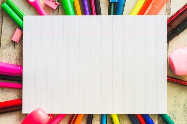Fiche de cahier entourée de crayons