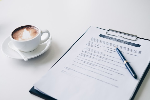 Fiche technique du contrat pen on insurance et document commercial, près de la tasse de café