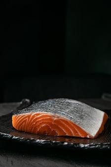 Fichier de saumon cru sur planche grise et surface noire