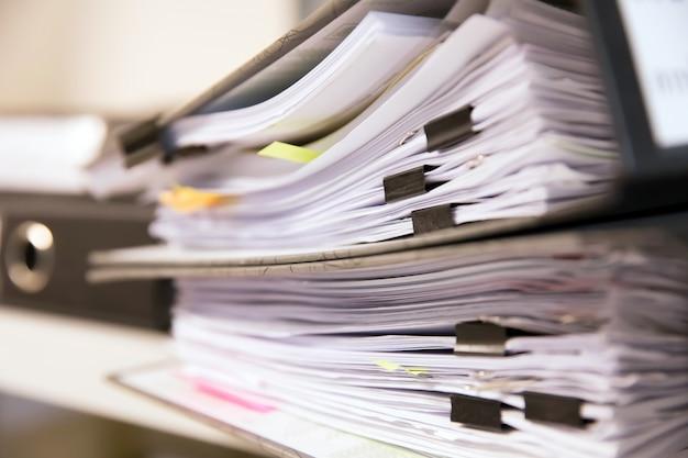 Fichiers de documents empilés sur des étagères.