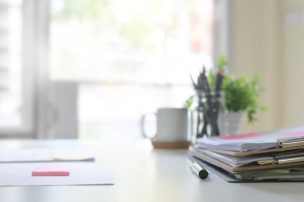 Fichiers de documents papier et matériel de bureau stylo sur la lumière de table et de bureau