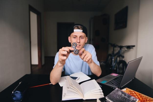 Fidget spinner entre les mains d'un jeune homme assis dans sa chambre au bureau. concentrez-vous sur le spin.