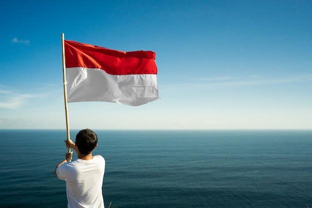 Fier homme indonésien sur une falaise de plage soulevant le drapeau de l'indonésie rouge et blanc