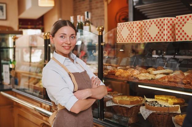 Fière boulangère souriant à la caméra, travaillant dans sa boulangerie, espace copie