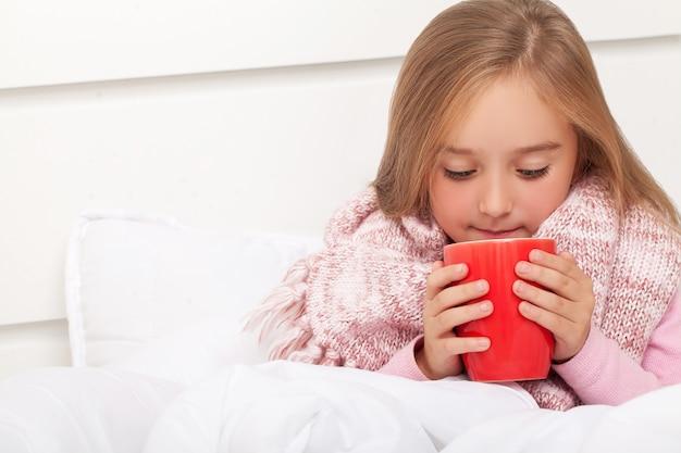 Fièvre, rhume et grippe médicaments et thé chaud à proximité, fille malade au lit