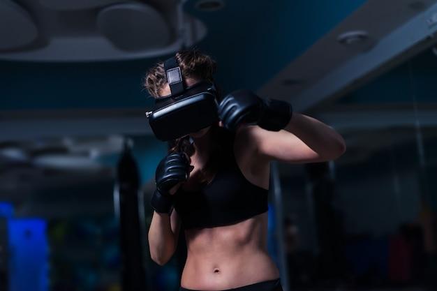 Fighter boxer fit girl punching in vr lunettes portant des gants de boxe dans la formation futuriste de jeu