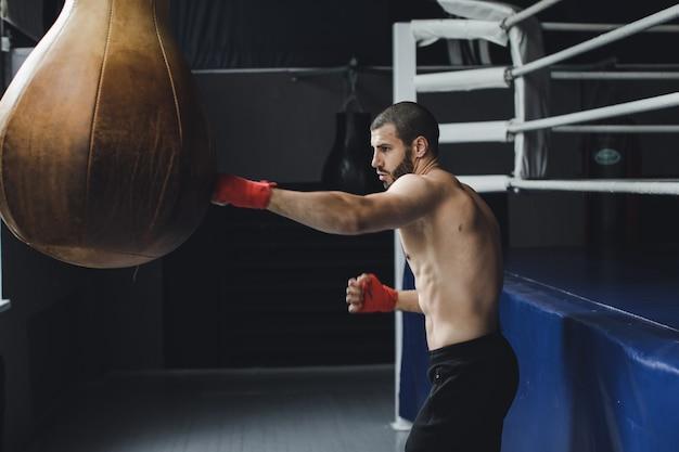 Fighter pratiquant quelques coups de pied avec sac de frappe sac de frappe coup de pied sur fond sombre sac de frappe noir pèse à la salle de sport images k de haute qualité