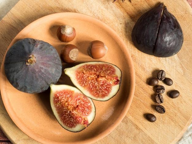 Figues sur une assiette avec des noix sur une planche à découper, surface en bois rustique