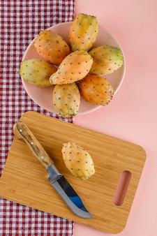 Figues de barbarie dans une assiette avec planche à découper et couteau sur tissu de pique-nique