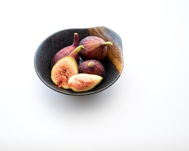 Figues biologiques dans un bol sur la table blanche