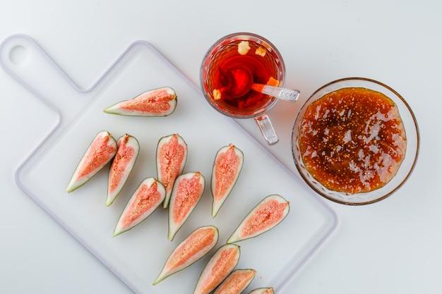 Figues avec confiture de figues, tisane, cuillère à thé vue de dessus sur blanc et planche à découper